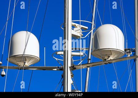 Detail of luxury white yacht with security camera and navigation equipment, radar and antennas on blue sky - Stock Photo
