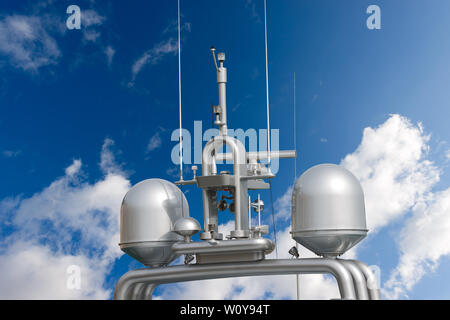 Detail of luxury grey yacht with navigation equipment, radar and antennas on blue sky with clouds - Stock Photo