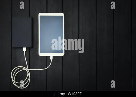 power bank loads tablet PC, smartphone - isolated on wooden background. charging concept. free copyspace - Stock Photo