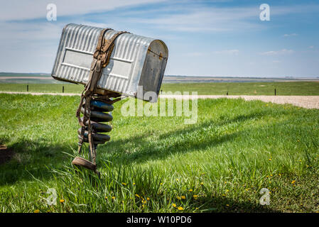 A row of three old metal farmers mailboxes on the prairies in rural Saskatchewan, Canada - Stock Photo