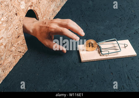 Man hand reaches for the coin bitcoin which is in a mousetrap. Concept, Finance and cryptocurrency. - Stock Photo