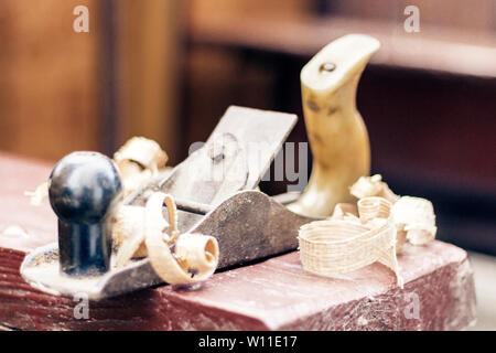 Joinery – old wooden plane and chips in a workshop of the carpenter, retro concept - Stock Photo
