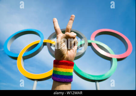 LONDON - MAY 4, 2019: A hand wearing LGBTQI pride rainbow colored wristband makes a peace sign in front of Olympic Rings standing under blue sky. - Stock Photo