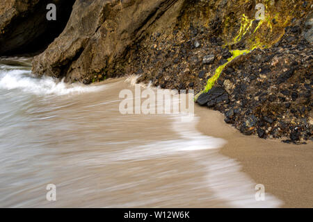 Crashing waves against rocks, moss and a cave in Laguna Beach, California. Long exposure - Stock Photo