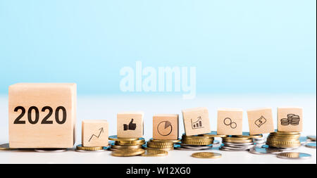 Wooden blocks with coins, dollar, graphs laying on real money - Stock Photo