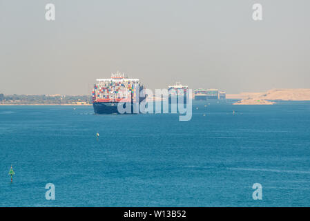 Suez, Egypt - November 5, 2017: Large container vessels (ship) passing Suez Canal in the sandy haze in Egypt. - Stock Photo