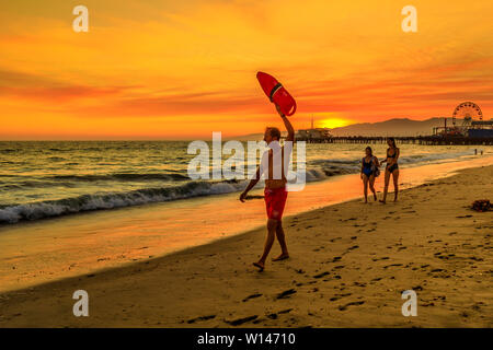 Santa Monica, California, USA - August 8, 2018: surf rescue baywatch lifeguard with lifesaver at sunset on seashore of Santa Monica Pier. Sunlight - Stock Photo
