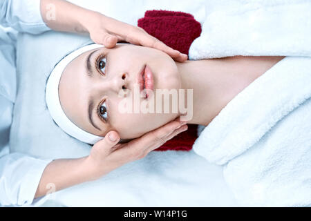 View from above of young pretty woman relaxing during massage of face in salon. Beautiful lady lying on coach and professional cosmetologist smoothing - Stock Photo
