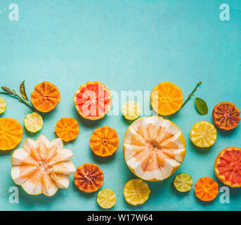 Various colorful citrus fruits halves with green leaves on light blue background, top view, border with copy space for your design. Flat lay. Healthy - Stock Photo