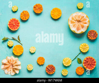 Frame of various colorful citrus fruits halves with green leaves on light blue background, top view. Copy space for your design. Flat lay. Healthy foo - Stock Photo