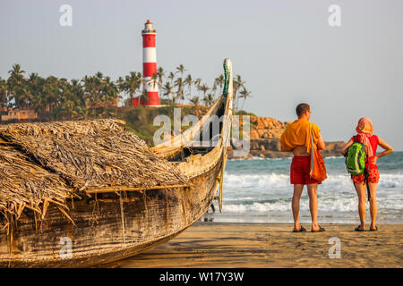 Kerala, India: Dated-June 14, 2019: A beach in Kerala Goa with a lighthouse in the background and a traditional fishing boat in the foreground. Foreig - Stock Photo