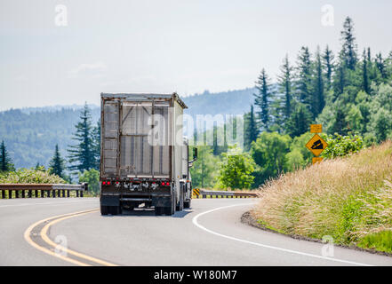 Big rig white day cab semi truck with roof spoiler transporting huge covered bulk semi trailer with ladder on the back wall moving on the turning wind - Stock Photo
