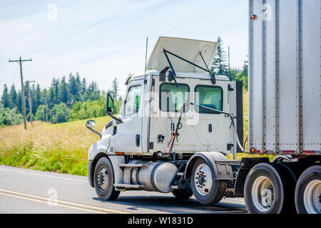 Big rig white day cab semi truck with roof spoiler transporting huge covered bulk semi trailer moving downhill on the turning winding road with yellow - Stock Photo