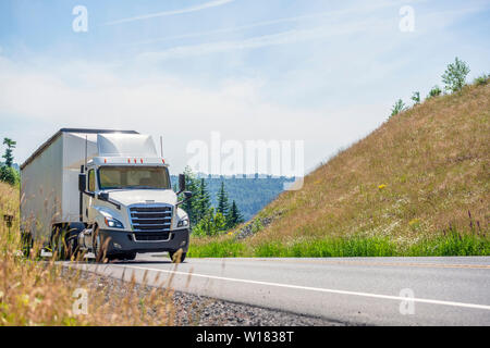 Big rig white day cab semi truck with roof spoiler transporting huge covered bulk semi trailer moving uphill on the turning winding road with yellow g - Stock Photo