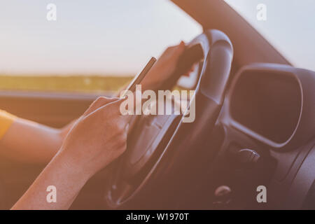 Dangerous texting while driving behavior, close up of female hands using mobile phone and operating motor vehicle on road through countryside, selecti - Stock Photo