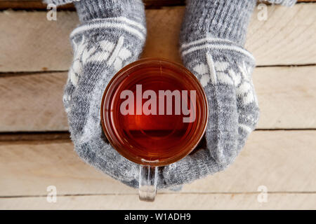 women's hands in warm gloves holding a glass of tea - Stock Photo