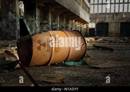 Radioactive warning on old rusty barrel in destroyed and forgotten building. Radiation symbol with russian alert on waste container after nuclear. - Stock Photo