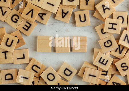 Top down view, pile of square wooden blocks with letters on white board. Three empty tiles for your text. - Stock Photo