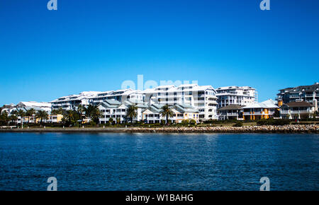 Large waterside houses built in front of condominium apartments with riverside grass frontage, stone retaining wall and blue river against clear blue - Stock Photo