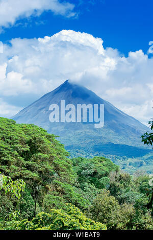 Arenal volcano behind tropical forest, La Fortuna, Costa Rica - Stock Photo