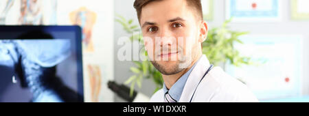Smiling male doctor working with compute in his office - Stock Photo