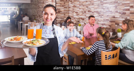 young waitress warmly welcoming guests to comfortable family cafe - Stock Photo