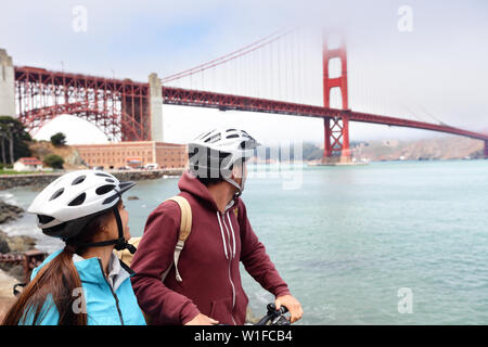 Golden gate bridge - biking couple sightseeing in San Francisco, USA. Young couple tourists on bike guided tour enjoying famous travel landmark in California, USA. - Stock Photo