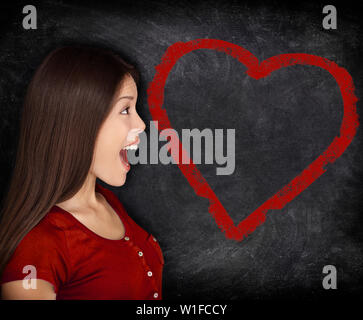 Heart love woman portrait on blackboard chalkboard background. Surprised Asian woman at heart shape drawing showing St-Valentines day concept. - Stock Photo