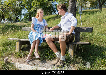 Teenage couple relaxing outdoors on park bench, Bavaria, Germany - Stock Photo