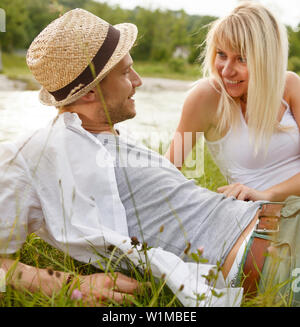 Young couple on the Isar riverbank, Munich, Bavaria, Germany - Stock Photo