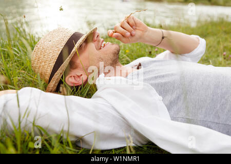 Young man lying on the Isar riverbank, Munich, Bavaria, Germany - Stock Photo