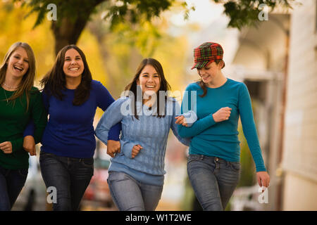 Girls linking arms and walking - Stock Photo