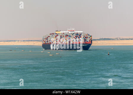 Suez, Egypt - November 5, 2017: An Large container vessel ship MSC Maya passing Suez Canal in the sandy haze in Egypt. - Stock Photo