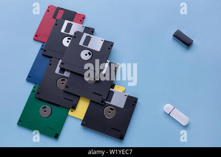 The evolution of digital data storage device. Floppy disks vs small flash drives. Isolated on a blue background. Modern and retro technology. - Stock Photo