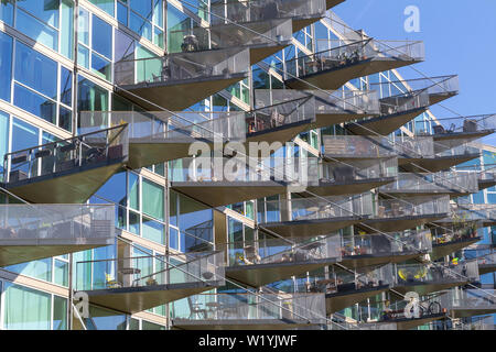 Modern architecture building in Orestad, Copenhagen, with triangular balconies in a glass facade - Stock Photo