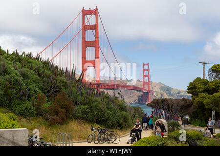 People walking around a park next to the Golden Gate bridge in the bay of San Francisco - Stock Photo