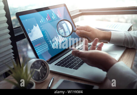 Business concepts with businessman holding magnifying glass with graph chart on computer laptop.For investment analysis,research market ideas - Stock Photo