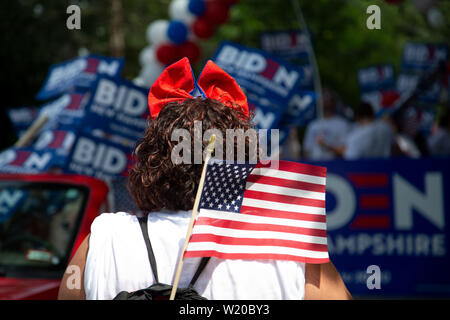 Amherst, NH, USA. 4th July, 2019. 2020 Presidential election candidates marched in the 4th of July parade on July 4, 2019 in Amherst New Hampshire. They all were campaigning to voters for support. A women carries an Aerican flag as she watches candidates go by. Credit: Allison Dinner/ZUMA Wire/Alamy Live News - Stock Photo