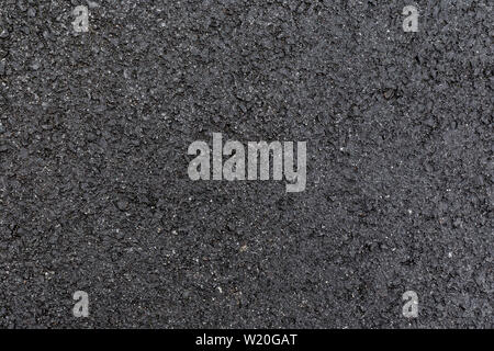 Close-up of wet, gray asphalt, viewed from above. High resolution full frame textured background. - Stock Photo