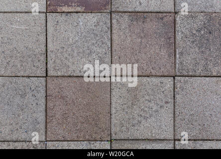 Close-up of a bit dirty and weathered square paving stones or blocks outdoors viewed from above. High resolution full frame textured background. - Stock Photo