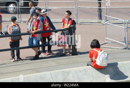 London, England, UK. Young Japanese schoolgirl sitting on her own by the Victoriaa Memorial in front of Buckingham Palace - Stock Photo