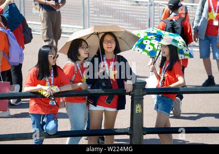 London, England, UK. Japanese schoolgirls on a hot, sunny day outside Buckingham Palace - Stock Photo