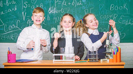 Group school pupils study chemical liquids. Girls and boy student conduct school experiment with liquids. Check result. School chemistry lesson. Test tubes with colorful substances. School laboratory. - Stock Photo
