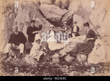 Victorian 1889 Photograph of a Family Sat on The Rocks on Borth Beach, Wales. This Fashionable Family are Having a Picnic. - Stock Photo
