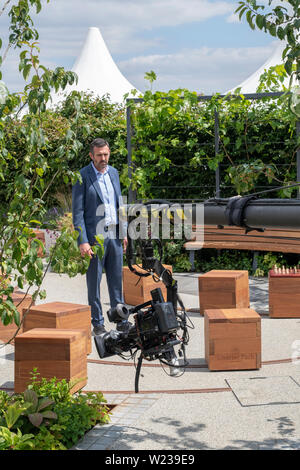 Adam Frost doing a piece to camera in a show garden at RHS Hampton Court flower show 2019. Hampton Court Palace, Surrey, UK - Stock Photo