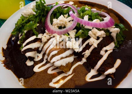 Close-up of a plate Delicious Mexican enchiladas with traditional mole of peanuts, cheese, lettuce, red onion and sour cream. Food made in a Mexico - Stock Photo