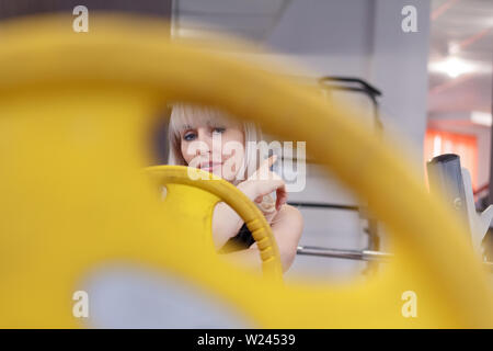 Blonde young woman looks into the camera through holes in a weight for a barbell, the concept of a healthy sports life, soft focus - Stock Photo