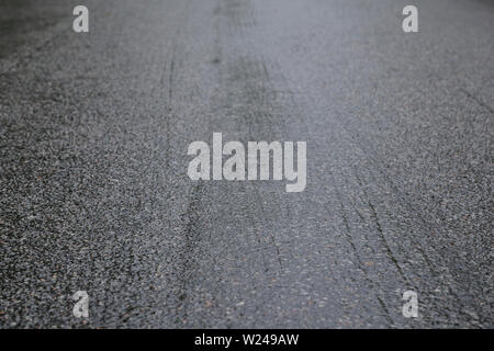 Wet asphalt road on a rainy day. Tilted angle, focused on the foreground. High resolution full frame background. - Stock Photo