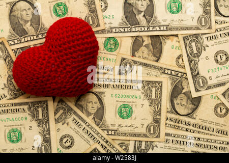 Red heart woven on dollar currency bills, love of money. - Stock Photo