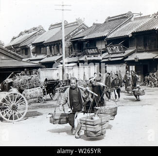 [ 1890s Japan - Nihonbashi Fish Market ] —   Men carry buckets with fish at the fish market in Nihonbashi, Tokyo in 1896 (Meiji 29). The market was destroyed by the Great Kanto Earthquake (Kanto Daishinsai) of September 1, 1923 (Taisho 12). It re-opened in Tsukiji in 1935 (Showa 10), where it remained until October 6, 2018 (Heisei 30).  20th century vintage glass slide. - Stock Photo